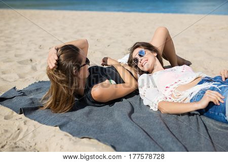 Two Beautiful Women Lying Together On Beach Laughing