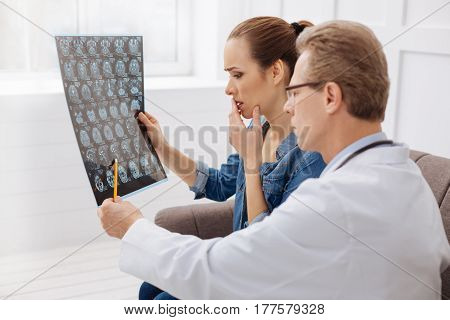 This must be treated immediately. Concerned focused professional neurosurgeon showing his patient her brain scan and pointing out some issues while she listening carefully