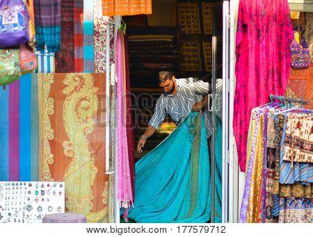 Munnar, Kerala, India - Circa November 2012 - Portrait of an unidentified apparel store owner folding fabrics in Munnar, Kerala, India