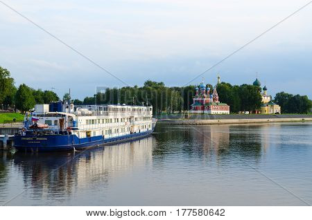"UGLICH RUSSIA - JULY 19 2016: Cruise three-deck motor ship ""Princess Anabella"" on river dock in Uglich Russia. In background - Church of Tsarevich Dmitry on Blood and Spaso-Preobrazhensky Cathedral of Uglich Kremlin"