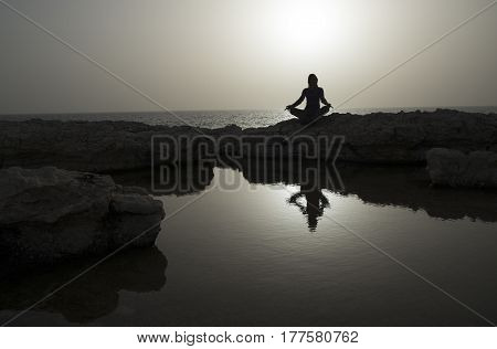 Woman sits as yogi on rock and meditates. Sea in background. Woman's silhouette reflects in water.