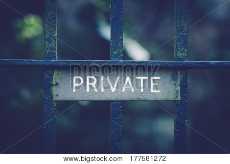 Private sign on an wrought iron gate with an antique filter applied to the image useful for privacy or security concepts