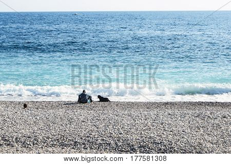 Nice, France - 25 February, A man with a dog on the beach, 25 February, 2017. People and tourists having a rest on the Cote d'Azur.