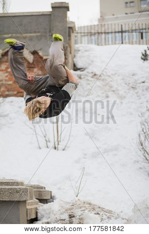 Teenager blonde hair guy training parkour jump flip in the snow covered park, telephoto