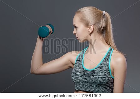 portrait of beautiful blonde girl in sportswear does exercises with dumbbells on a dark background