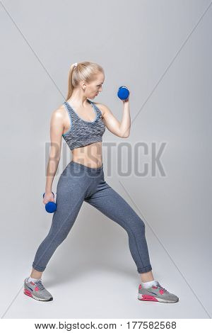 beautiful blonde girl in sportswear does exercises with dumbbells on a grey background
