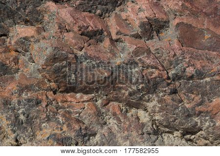 Texture of red-brown stone with cracks close-up