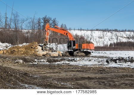orange digger with fang ripper in winter