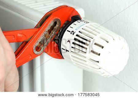 a worker is mounting a thermostat on heating