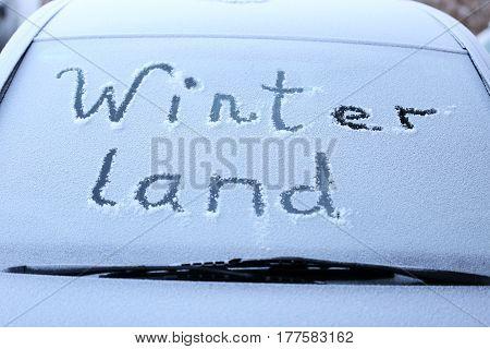 winterland text on a snowy car windscreen