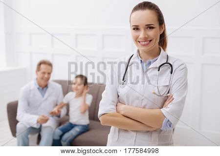 On guard of your health. Charming joyful professional doctor posing in her office while her colleague comforting her little patient after a successful injection