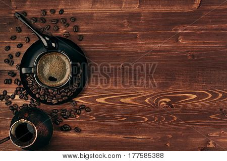 Hot coffee in black cup with beans spoon and turkish pot cezve with copy space on brown old wooden board background top view. Rustic style.