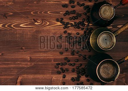 Hot coffee in shabby turkish pots cezve with crema beans with copy space on brown old wooden board background top view. Rustic style.
