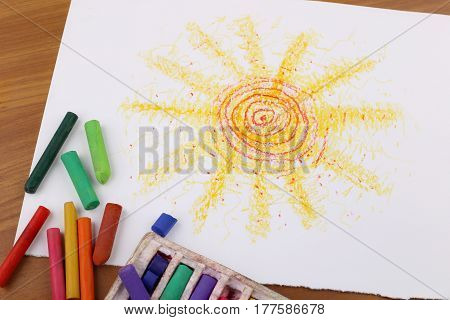 Drawing with pastel crayon. Crayon pieces and drawings on table. Hand drawn sun