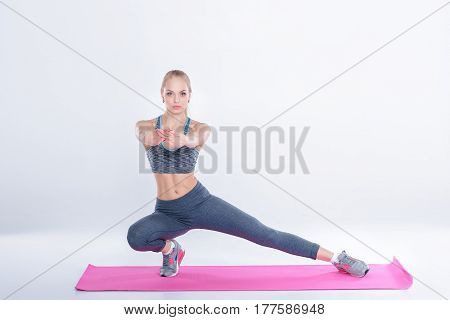 beautiful blonde girl in sportswear does exercises on a fitness Mat on a gray background. stretching