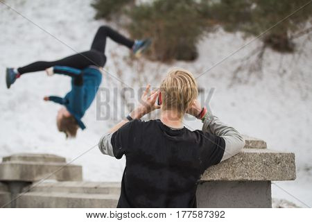 Blonde hair teenager makes photo on smartphone of acrobatic jump girl in winter city park - parkour concept, de-focused