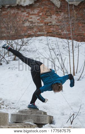 Teen girl jumping flip in snow winter park - free-run parkour concept, telephoto