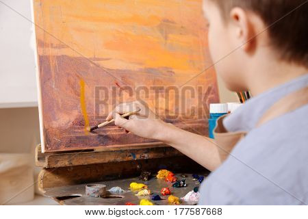 My artistic hobby. Young talented inspired boy sitting in the art studio and painting while expressing concentration and demonstrating his talent