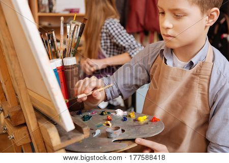 Talented young generation. Cute concentrated capable boy sitting in the art school and painting while showing his talent and using pallet