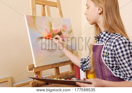 Expressing myself. Talented concentrated skilled girl sitting in the art school and painting while showing her skills and holding pallet