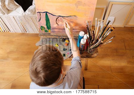 Painting the landscape. Young capable skilled boy sitting in the art school and painting while showing his talent and using pallet
