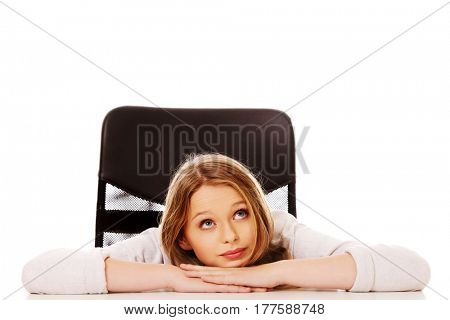 Young pensive woman sitting at the desk