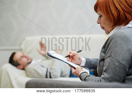 Middle-aged patient lying on comfortable sofa and describing his feelings about existing situation to concentrated psychologist with clipboard and pen in hands