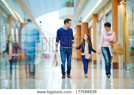 Family of three spending weekend in shopping center