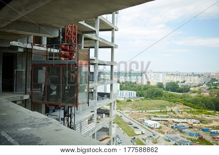 Unfinished concrete construction and engineers working in lift stage near by