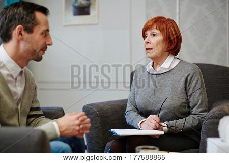Middle-aged male patient sitting on armchair and holding his hands together while mature psychologist giving him advice