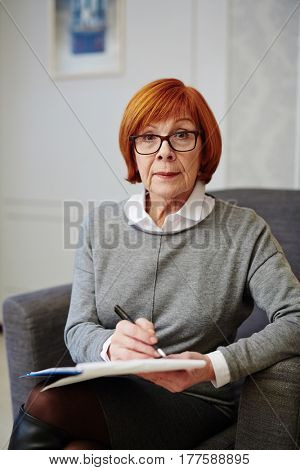 Portrait of mature psychologist in eyeglasses sitting on comfortable armchair with legs crossed and filling in medical card of patient