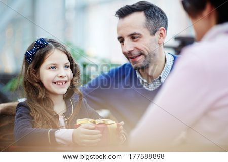 Happy youngster with gift-box looking at her mother with smile