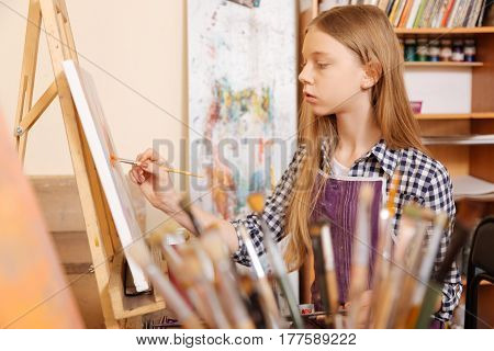 Enjoying my art class. Attentive skillful young girl sitting in school and having art class while showing her skills and holding paintbrush