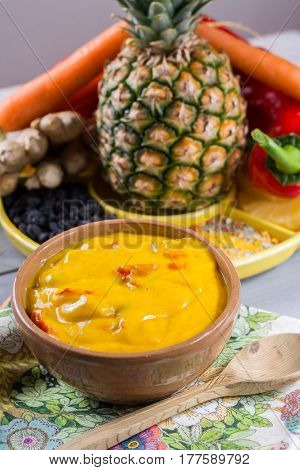 Bowl of vegetable curry sauce and ingredients that go into making it - paprika chili pepper carrot pineapple ginger. Used widely in Indian food.