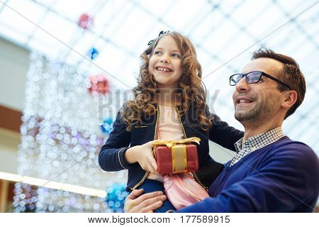 Happy man and his daughter saw something interesting during walk in shopping center