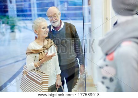 Retired couple standing by display window and discussing new collection of clothes