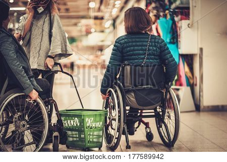 Young girl helping two disabled women in wheel chair in a department store