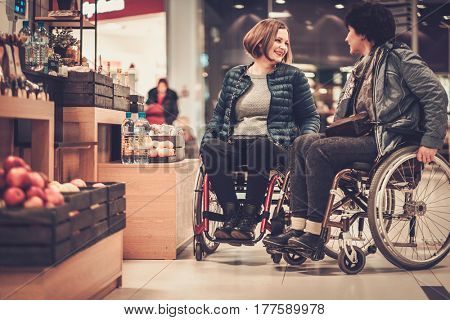 Two disabled women in wheel chair in a department store