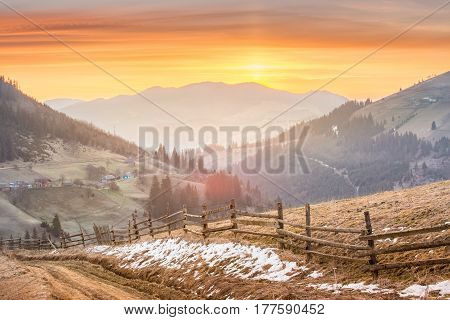 sunrise in a mountain village. mountain landscape. sun rises in the yellow sky