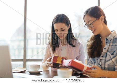 Serious businesswomen with packed gift-boxes