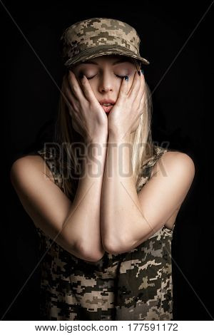 portrait of a beautiful blond woman soldiers in military attire on black background. sadness and despair
