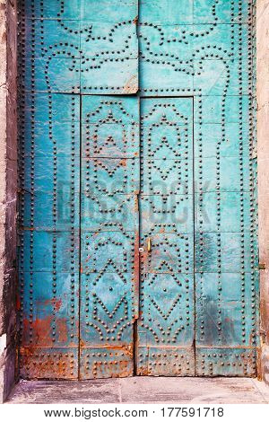 Ancient wooden blue door with decoretive elements and rivets