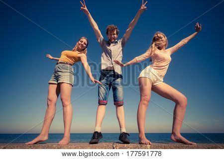 Friendship happiness summer holidays concept. Group of friends boy two girls having fun outdoor stretching arms celebrating wide angle view