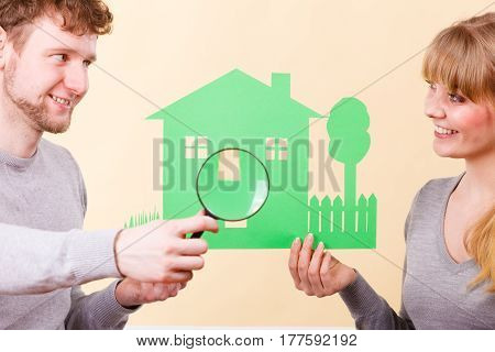 Home real estate credit mortgage concept. Cheerful couple with house. Young man and woman holding building cutout and magnifying glass.