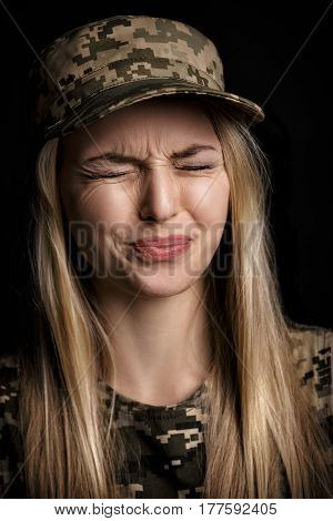 portrait of a beautiful blond woman soldiers in military attire on black background. emotion disgust