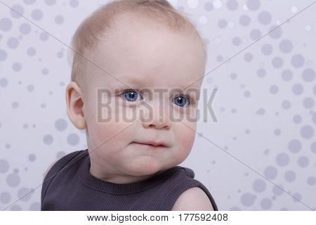 Handsome infant boy looking at camera on the abstract background. Horizontal indoor shot. Copy space