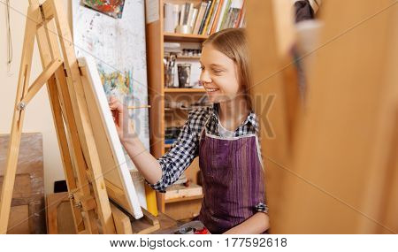 Delightful hobby. Skilled smiling lively girl sitting in the art studio and having art class while holding pencil and drawing