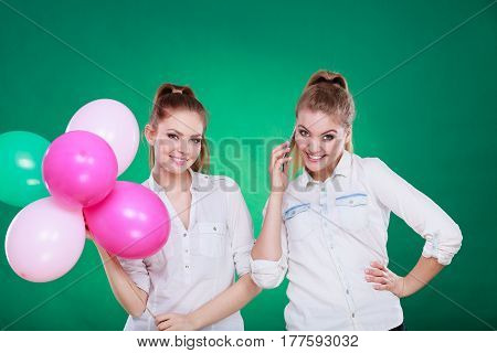 Happy joyful two girls having fun playing with colorful balloons and talking on mobile phone. Holidays celebration friendship and technology concept.