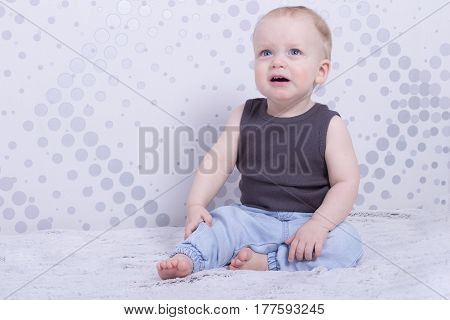 Sad crying handsome toddler boy sitting and looking away. Copy space. Indoor shot