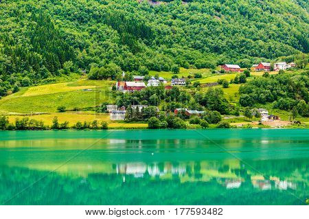 Norwegian country house in the mountains on sea shore. Beautiful coastline fjords landscape and village Scandinavia Europe